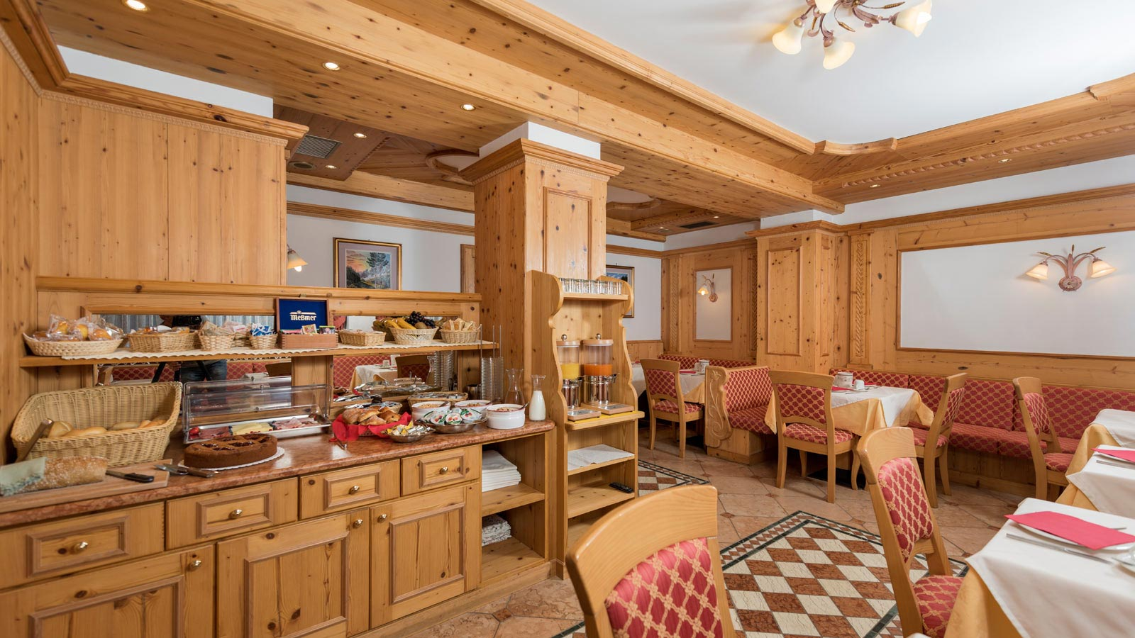 View of the dining room with Alpine-style furniture of the Hotel International in Val di Fassa
