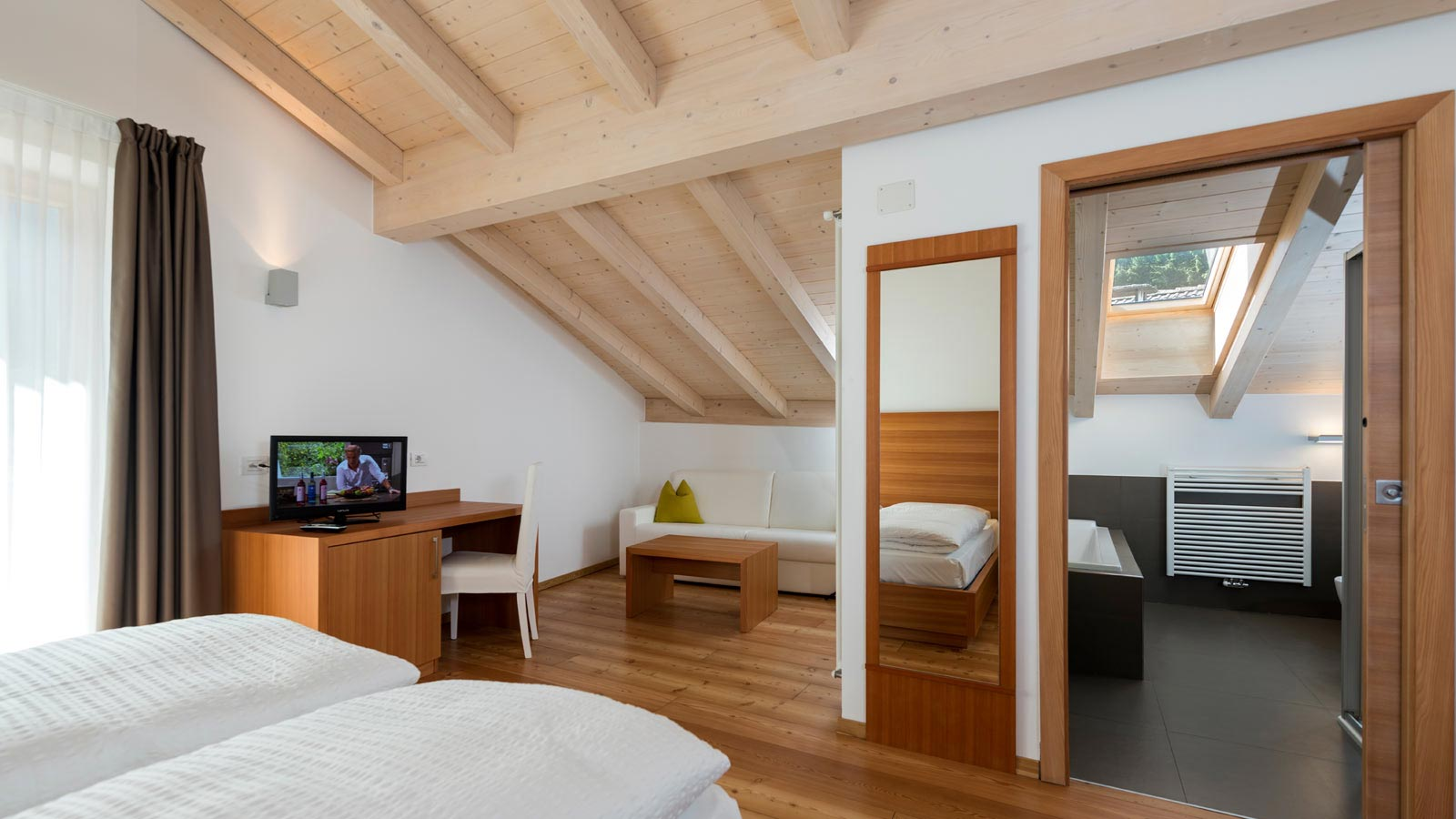 A double room at Garnì International with sofa corner, bathroom and exposed beams