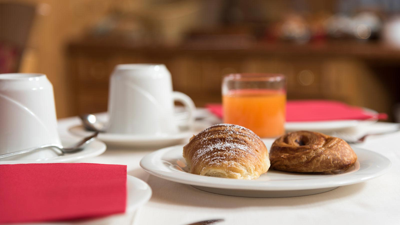 Table set for breakfast with croissants and orange juice