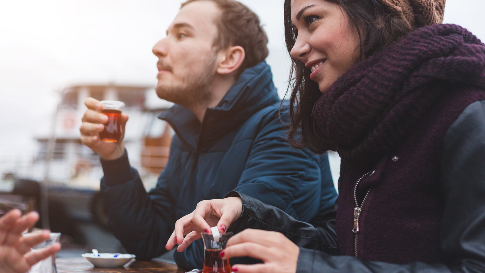 A boy and a girl sitting at a table outside drinking a glass of hard liquor